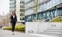 businesswoman-commuting-to-work-talking-on-mobile-phone-outside-modern-office-building.jpg